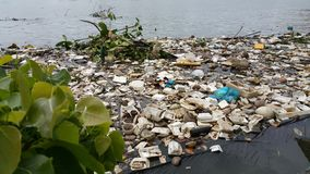 Plastic pollution in water. Plastic pollution in water with Styrofoam products and others stock images