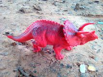 Red dinosaur. Animal toy on ground nature Royalty Free Stock Images