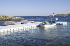Plastic pontoon with two covered boats and fishing boat Stock Photography