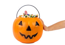 A plastic pumpkin filled with candy and hand of kid,  isolated Stock Image