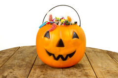 A plastic pumpkin filled with candy on wooden table Stock Photos