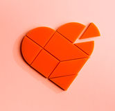 Plastic puzzle in the form of heart with disconnected piece on a pink background. Plastic orange puzzle in shape of heart with disconnected piece on pink Royalty Free Stock Photos