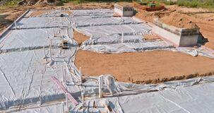 Plastic water pipes industrial pipeline laid on sand foundation at construction site