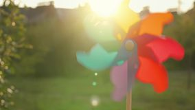 Plastic rainbow windmill rotates against the setting sun stock video