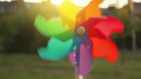 Plastic rainbow windmill rotates against the setting sun