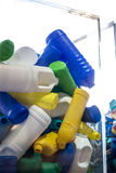 Plastic recycling. A pile of blue, yellow, white and green plastic  containers of different sizes and shapes behind a transparent wall,  awaiting recycling Royalty Free Stock Image