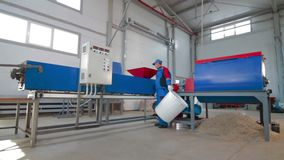 Worker loads sliced plastic in automated plastic recycling machine. Plastic recycling. Worker at recycling plant stock video