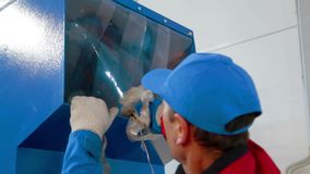 Worker loads sorted plastic in automated plastic recycling machine. Plastic recycling. Worker at recycling plant stock footage