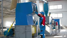 Worker loads sorted plastic in automated plastic recycling machine. Plastic recycling. Worker at recycling plant stock video footage