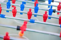 Plastic red and blue football players on table. Table soccer match between blue team versus red team Royalty Free Stock Images