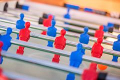 Plastic red and blue football players on table. Table soccer match between blue team versus red team Stock Image