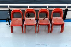 Deck of the ship and chairs. Plastic red chairs for passengers on the deck of a pleasure excursion boat stock images