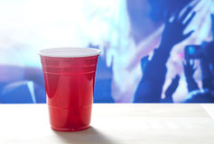 Plastic red party cup on a table. Nightclub full of people dancing on the dance floor in the background. Disco lighting. Perfect for marketing and promotion Stock Images