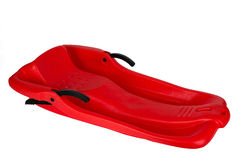 Plastic red sled for skiing on white background Stock Photos