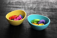 Plastic Rings in Bowls. On Wooden Background stock images