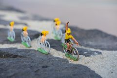 Plastic yellow road cyclists outdoor. V shape. Competition. Peloton. Plastic road cyclists. Yellow jerseys. Competition concept. Teamwork and leadership royalty free stock photo