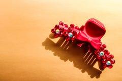 Plastic rode haarklem met met bergkristallen op de bronsachtergrond royalty-vrije stock foto's