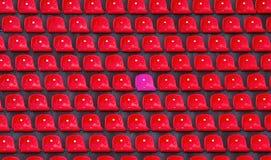 Plastic rood en roze zetels één op voetbalstadion stock fotografie