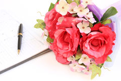 Plastic roses pen and notebook,Fake roses Stock Photography