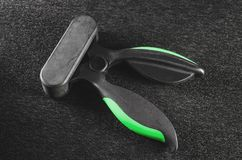Plastic and rubber hand grip for exercise hand and forearm. Black and green expander gripper Stock Photography