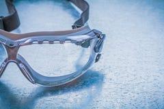Plastic safety glasses on metallic background Stock Image