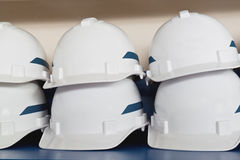 Plastic safety helmets. Stack of white plastic safety helmets with blue strip Royalty Free Stock Photography
