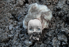Plastic scald doll head lying in a pile of dirt Stock Photo