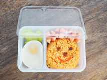 Plastic school lunch box for kids with funny face of fried rice. And egg on wood background.Bento packed stock photography
