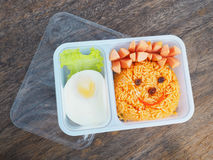 Plastic school lunch box for kids with funny face of fried rice. And egg on wood background.Bento packed stock photos