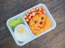 Plastic school lunch box for kids with funny face of fried rice. And egg on wood background.Bento packed royalty free stock images