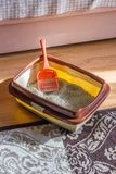 Plastic scoop in a cat litter box, standing on a floor. Plastic scoop in a cat litter box, standing on a floor royalty free stock photos