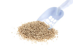 Plastic scoop for cleaning cat litter and a pile of filler on a white background Stock Images
