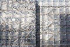 Plastic sheeting on scaffolding. Weatherproof plastic sheeting covering scaffolding to protect the workers Stock Image