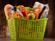 Plastic shopping basket with assorted gorcery products Stock Image