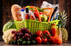 Plastic shopping basket with assorted gorcery products Royalty Free Stock Photo