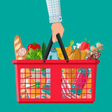 Plastic shopping basket full of groceries products Royalty Free Stock Images