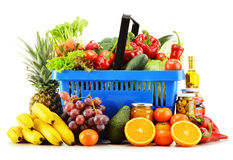 Plastic shopping basket with groceries on white Stock Image