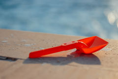 Plastic shovel on pool edge Royalty Free Stock Image