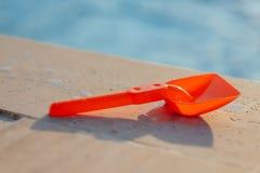 Plastic shovel on pool edge Royalty Free Stock Photography