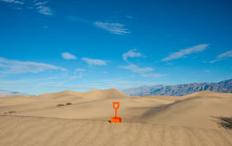 Plastic Shovel Standing in a Sand Dune Royalty Free Stock Photo