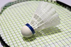 Plastic shuttlecock of badminton put on the green net of badminton racket. stock photos