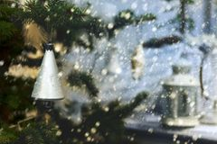 Plastic silver colored bell on evergreen tree on background of snowing and lamp on porch. Retro style. Plastic silver colored bell on evergreen tree on Stock Photos