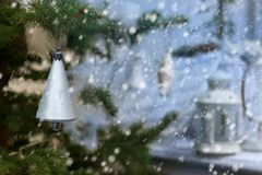 Plastic silver colored bell on evergreen tree on background of snowing and lamp on the porch. Small DoF focus put only to bell. Small DoF focus put only to Royalty Free Stock Images