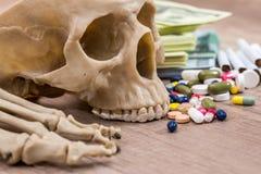 Plastic skull of dollars, pills, drugs Stock Images
