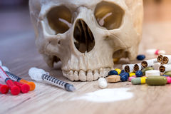 Plastic skull with pills, drugs and syringes Stock Photo