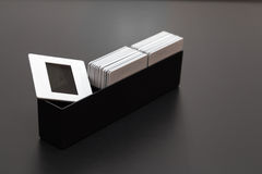 Plastic slides film diapositives Box. Old memories kept in 35mm diapositives inside their black plastic box above a dark grey background stock photography