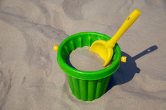 Plastic spade and bucket in sand Stock Photography