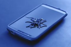 Plastic spider toy in action of running on surface of cell phone. stock illustration