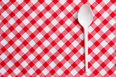 Plastic spoon on checkered tablecloth Royalty Free Stock Image