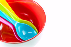 Plastic spoon. Colorful plastic spoons in red bowl on white background Stock Images